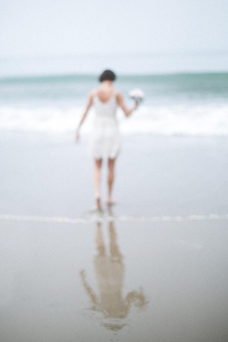 Soft focus, fine art image of a bride on summerland beach during her wedding
