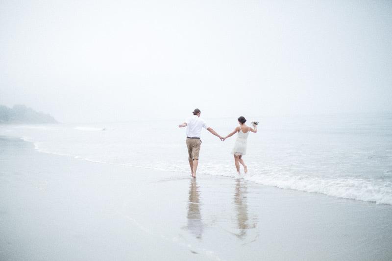 Playful, outdoorsy couple on summer land beach before their summer land beach wedding
