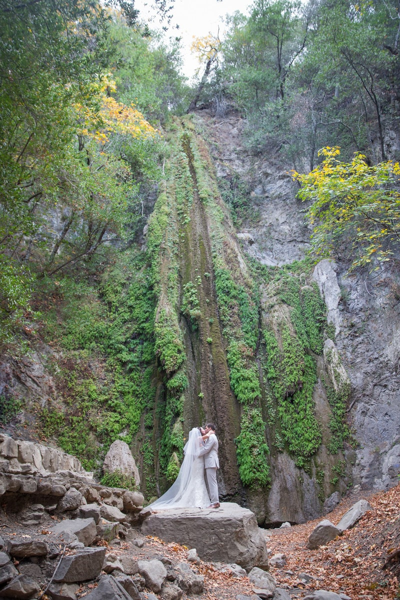 Beautiful fall colors surround these newly weds kiss during Woodsy Nojoqui Falls Elopement.