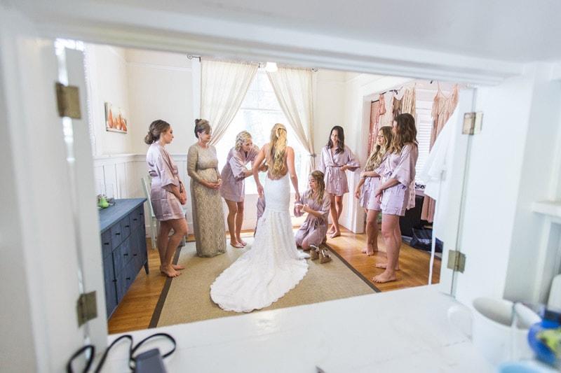 Bridesmaids helping bride into her wedding dress for a Napa wedding at Tres Sabores Winery