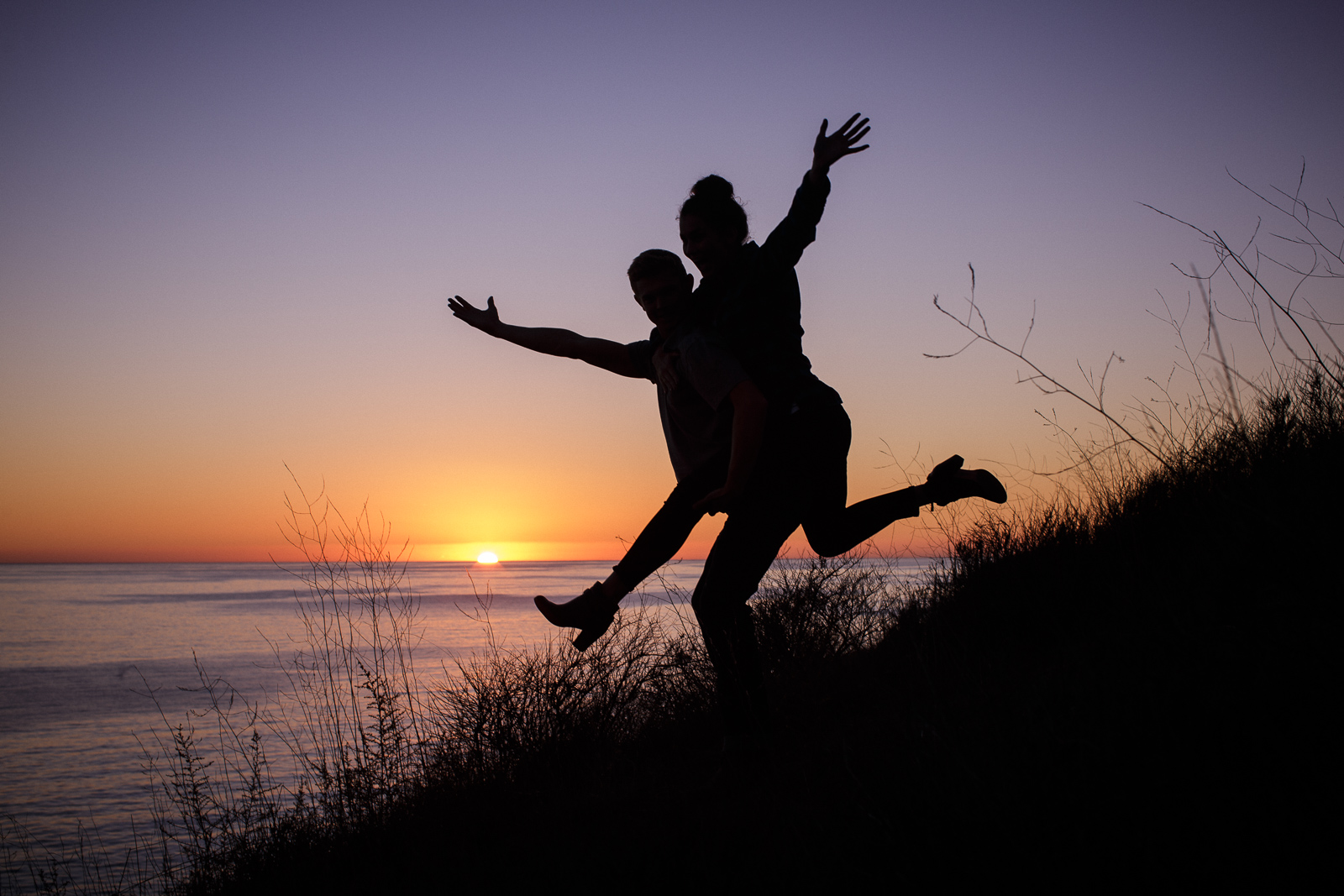 Silhouettes at sunset during California coast engagement on the Gaviota Bluffs