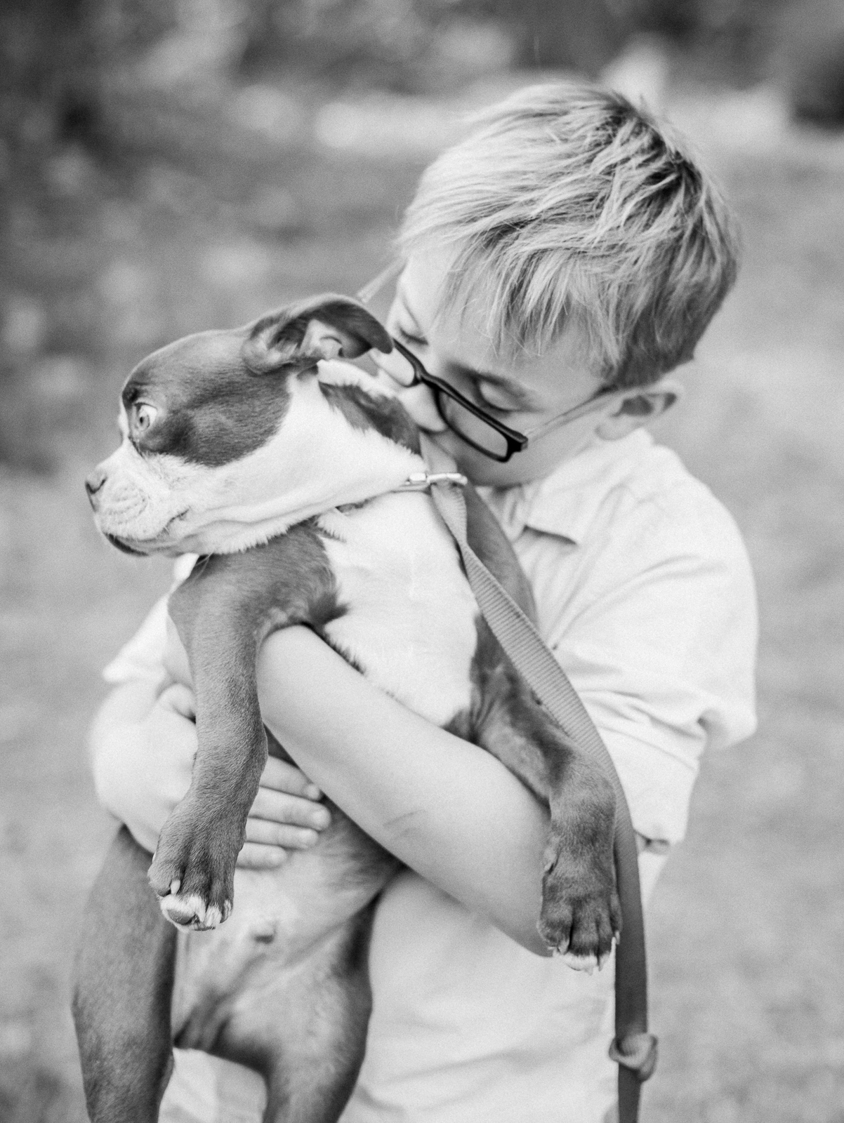 black and white photo of boy with his new puppy
