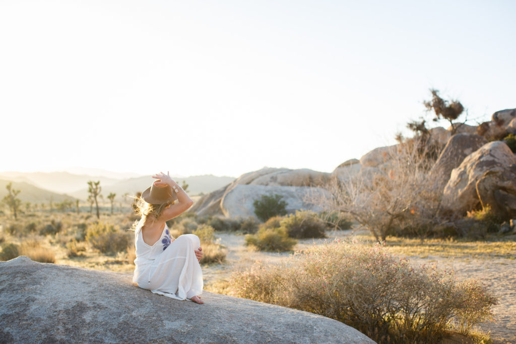 Taking in the view, keeping track of her hat as sun hits the horizon in Joshua Tree